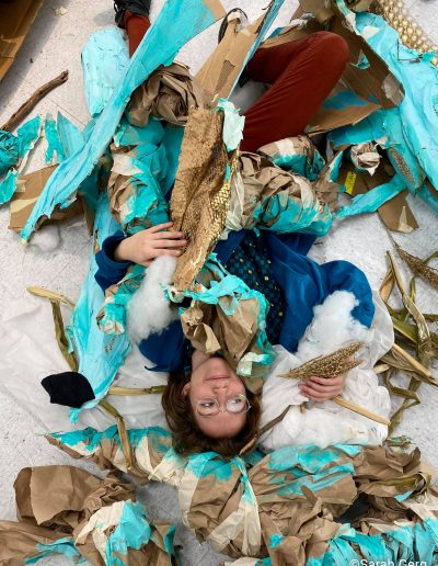 Artist lying on floor amidst pieces of giant sculpture