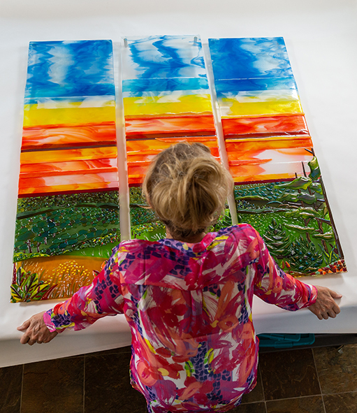 Barbara Westfall in front of Mountain Sunset Triptych, art glass