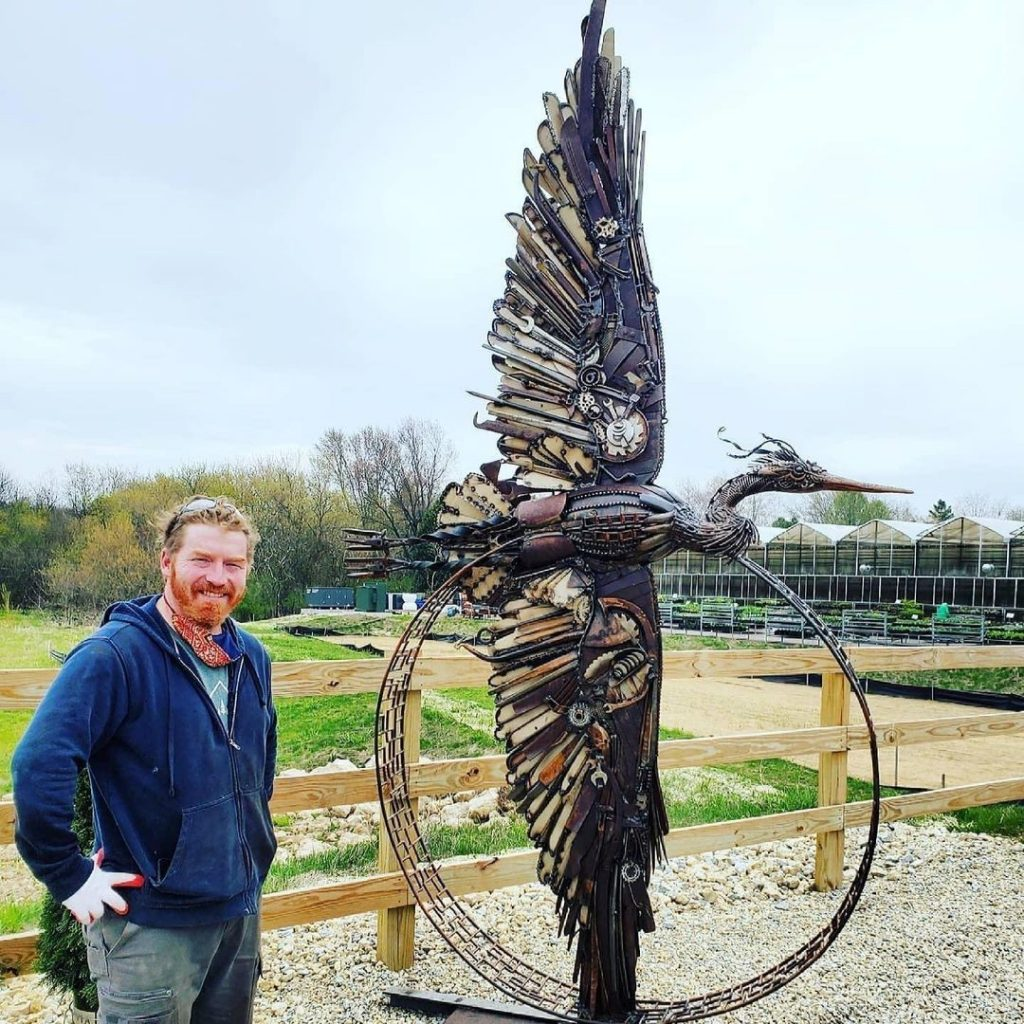 John Pahlas beside his giant Heron scupture at K&A Greenhouse